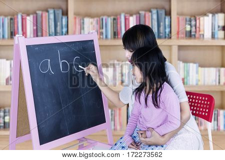 Picture of little girl learns alphabet with her teacher writing the letter on chalkboard shot in the library