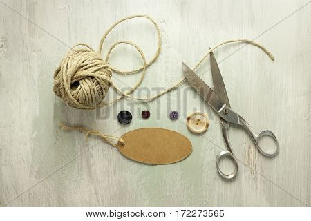 A photo of vintage scissors with a roll of twine, a tag with copy space, and buttons, shot from above on light wooden boards background texture