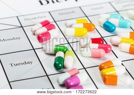 pills of different colors on a calendar medication