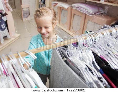 Child in a children's store. Happy girl choosing clothes
