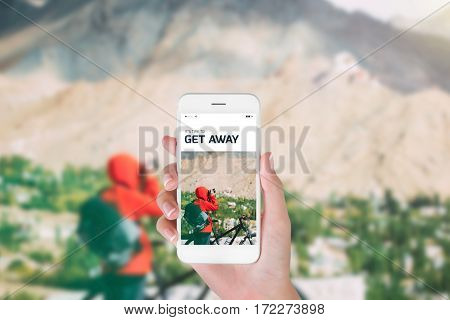 woman using her smartphone for searching the travel information of bike cycling and taking photo in the Himalayan range Leh Ladakh India. Traveling concept Himalayan range blurry background.