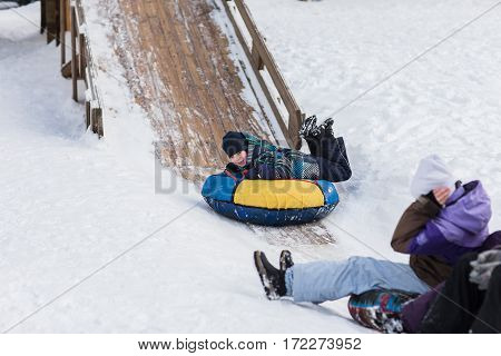 A happy child is heading to ice mountain for tubing in children in the winter.