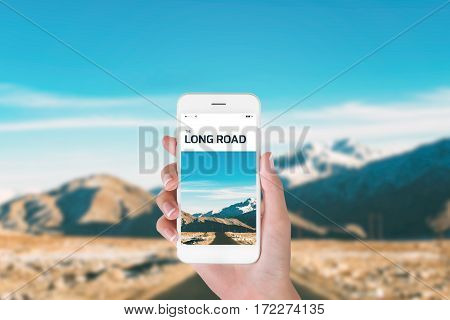 woman using her smartphone for searching the travel information of long road in Himalayan range winter season Leh Ladakh India. Traveling concept Himalayan range blurry background.