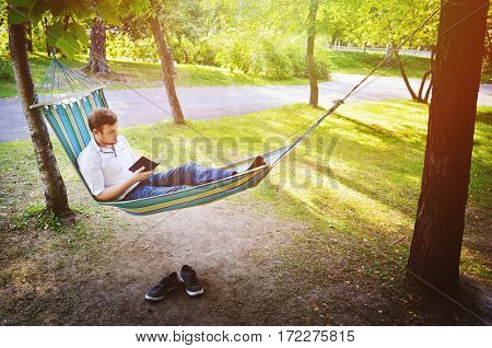 A man is reading a book under the trees