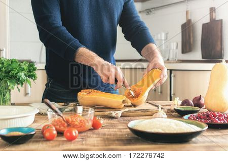 Man cooking a butternut squash on a wooden table in the home kitchen. Man cooking a butternut squash on a wooden table in the home kitchen. Concept of healthy eating and lifestyle