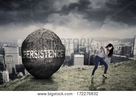 Female entrepreneur is pulling a big stone with persistence word while walking on the hill