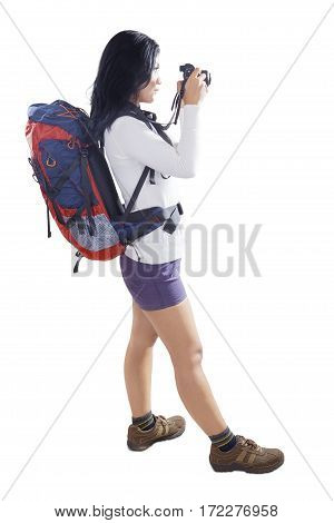 Young woman photographer carrying backpack and taking photos with digital camera in the studio