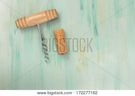 A photo of an old-fashioned corkscrew with a cork, shot from above on a teal background texture with plenty of copy space. A design template for a wine list or a tasting invitation