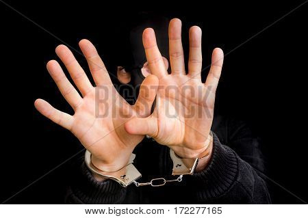 Masked Thief In Handcuffs Isolated On Black Background