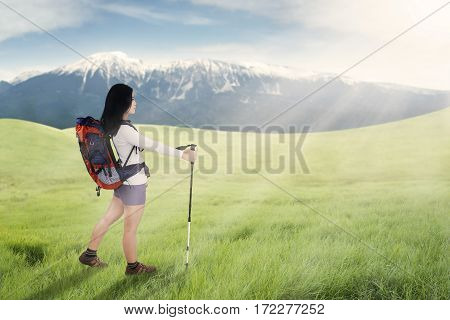 Young female hiker carrying backpack while walking on meadow with hiking stick