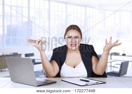 Portrait of female worker confused with her job while sitting in front of her laptop and clipboard