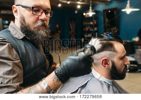 Stylist shaving client head side view. Stylish bearded barber making hairstyle for youn man in barbershop interior. Beauty, modern lifestyle, style, concept