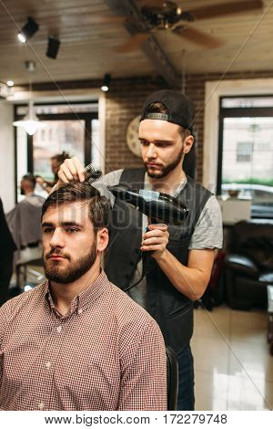 Stylist making modern hairdo for young man. Successful businessman sitting at barber shop and dry hair. Style, beauty, modern life concept