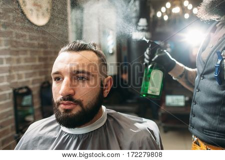 Last step of haircut - barber spray client free space. Portrait of young man sitting at barbershop and making stylish hairdo. Beauty, modern life, business concept