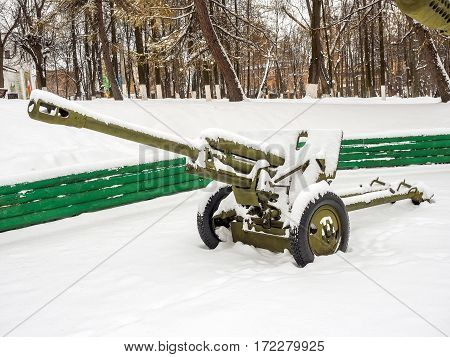 Anti-tank guns covered with snow at the park during the winter.