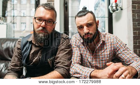Hipster and biker sitting together portrait. Two bearded men with different hobbies, but similar style. Generation, trend, subculture, fashion, lifestyle concept