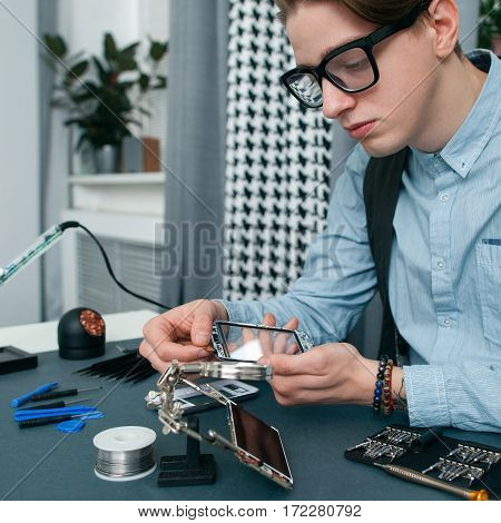 Serious young man fixing mobile phone free space. Attentive geek in glasses examing broken smartphone, repair shop workplace with tools. Electronic fixing, modern technology, business concept