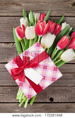 Colorful tulips bouquet and gift box on wooden background. Red and white. Top view