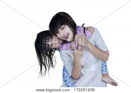 Cheerful young mother and her daughter doing piggyback ride in the studio isolated on white background
