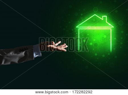 Hand of businessman touching with finger glowing home icon or symbol