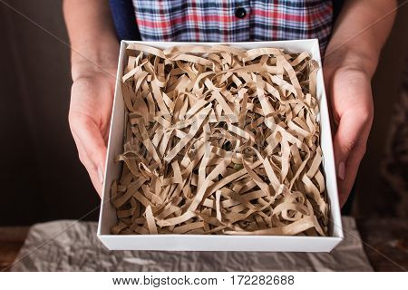 Empty gift box in female hands closeup void. Unrecognizable woman holding postal package with wooden shavings. Background for shopping, delivery advertisement, mockup