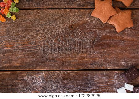 Empty wooden table with sweets flat lay. Top view on rustic table with gingerbread star cookies and chocolate pieces, free space. Confectionery, dessert, pastry, sugar concept