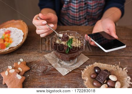 Modern technologies in everyday life concept. Unrecognizable woman using smartphone while eating sweet dessert in restaurant, Lifestyle, social network concept
