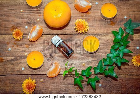Citrus and herbs aroma oil concept. Essential glass bottle, tangerine, yellow aroma candles , orange daisy flowers  and ivy branch with green leaves on a wooden background