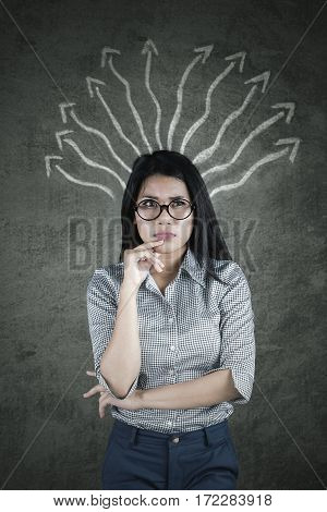 Pensive businesswoman looking at the camera while thinking with many arrows on the blackboard