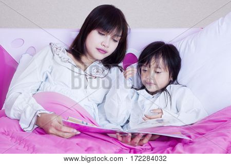 Portrait of young mother and her daughter reading a storybook together in the bedroom