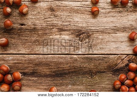Wooden background with hazelnuts frame flat lay. Top view on rustic table with brown filbert nuts border, free space, bright autumn backdrop. Harvest, fall, food ingredient concept