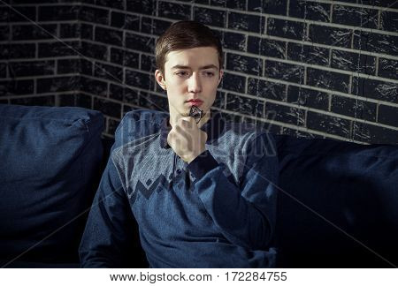 Portrait of handsome serious and pensive young man, wearing jersey jumper, holding glasses,  sitting on the sofa in a room with dark brick wall