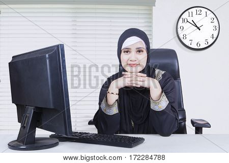 Thoughtful businesswoman wearing Islamic clothes and looking at the camera while working with computer