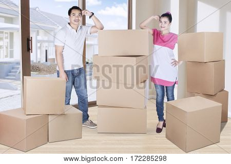 Portrait of young woman and man standing besides pile of boxes while looking at the camera