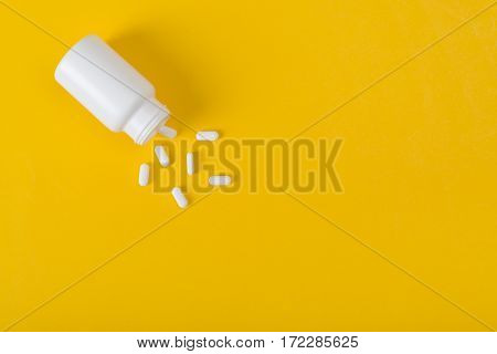 White pills and white bottle with copy space on yellow background Healthy and Medicine concept.