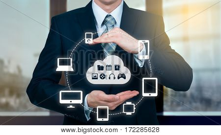 Businessman holding a cloud connected to many objects on a virtual screen concept about the internet of things.