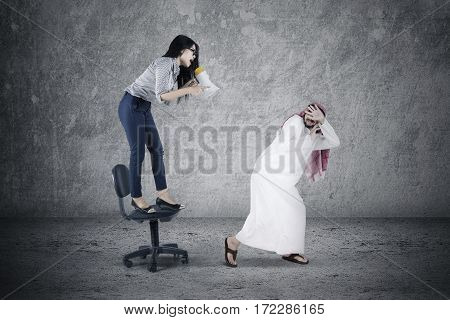 Picture of young businesswoman shouting to her arabian employee with a megaphone while standing on the chair