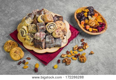 Oriental Sweets. Assorted traditional turkish delight Rahat lokum on gray stone background. Rahat Lukum (lokum) sprinkled with coconut sugar and sesame. Dried figs raisins prunes nuts.