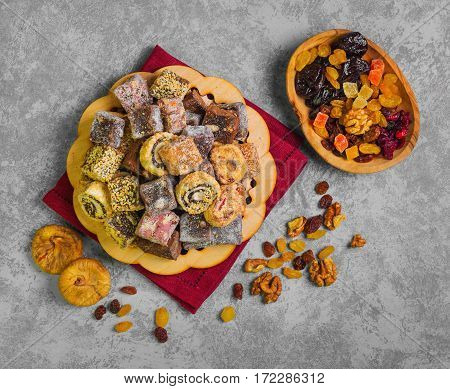 Oriental Sweets. Assorted traditional turkish delight Rahat lokum on gray stone background. Rahat Lukum (lokum) sprinkled with coconut sugar and sesame. Dried fruits figs raisins prunes nuts.