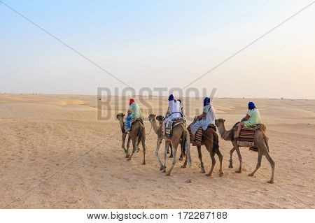 Camel caravan with riding tourists in Sahara desert, Tunisia