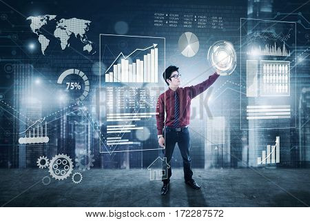 Young businessman pressing virtual icon with financial statistics on the digital screen