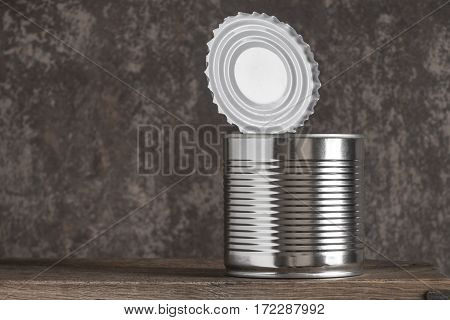 Open tin can is on the board on a background of a concrete wall