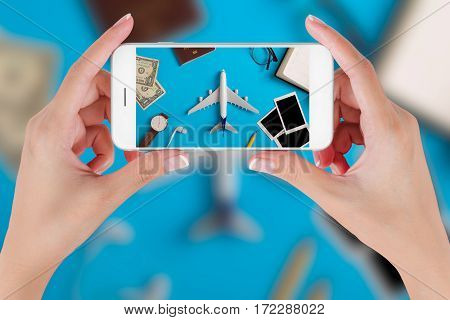 Woman hand using smart phone taking photo for preparation Traveling with watch airplane money passport pencils book earphone Blank photograph and eyeglass. Travel concepts Ambient blurry background.