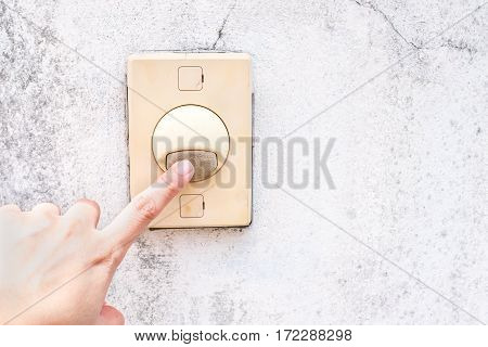 Female Hand Press On Buzzer On Grunge Wall N Front Of House