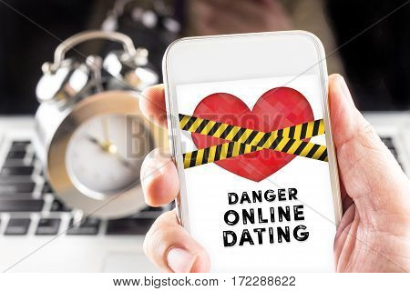 Hand Holding Mobile With Caution Tape On Heart And Danger Online Dating  On Screen With Clock And La
