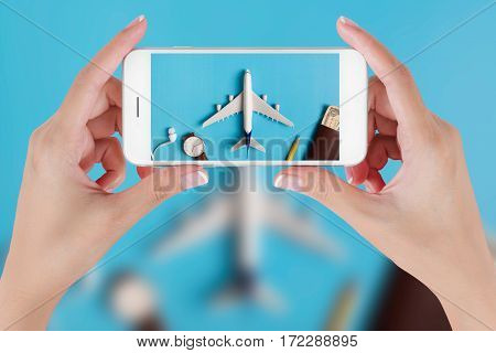 Woman hand using smart phone taking photo for preparation traveling with watch airplane money passport pencils and book. Travel concepts Ambient blurry background.