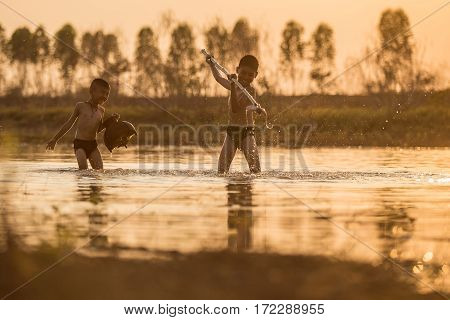 Asian boy fishing in a river, thailand .