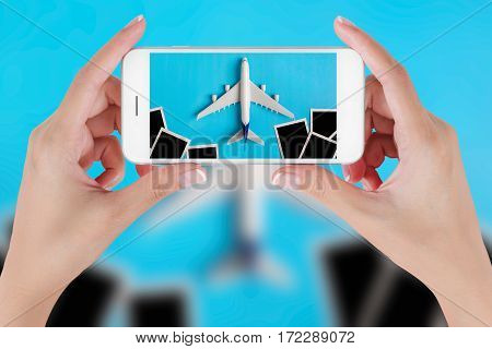 Woman hand using smart phone taking photo for preparation traveling with airplane model and blank photograph. Travel concepts Ambient blurry background.