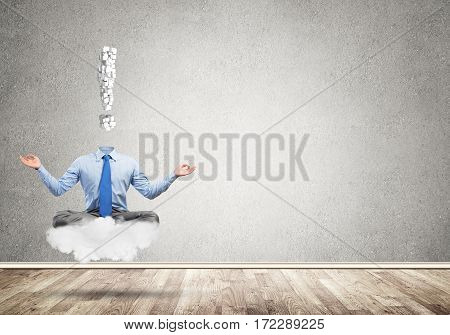 Businessman sitting in lotus pose and exclamation mark instead of his head