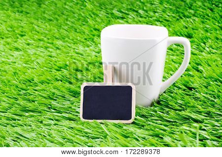 White Coffee Cup And Blackboard Clip On Grass,template For Adding Text